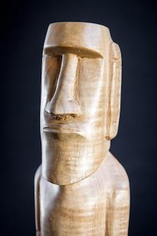 Tradycyjna drewniana rzeźba moai z wyspy wielkanocnej. ciemne tło