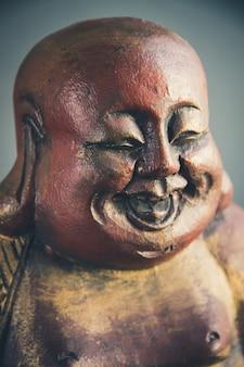 Tradycyjna drewniana statua chińskiego buddy na ciemnym tle