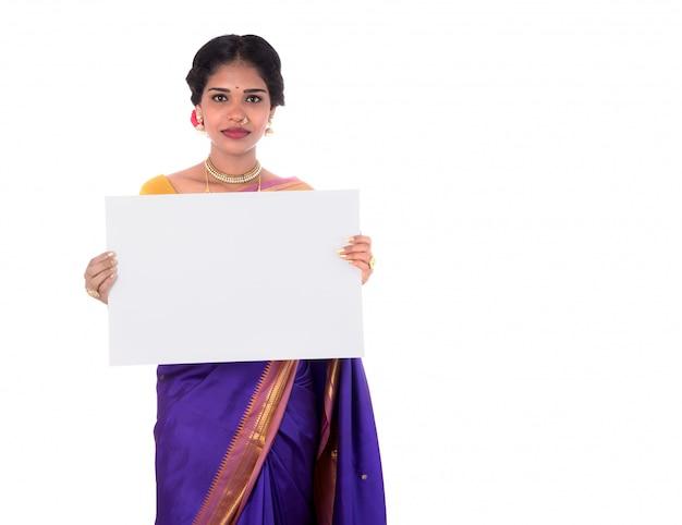 Tradycyjna dziewczyna trzyma pustą bielu znaka deskę i pokazuje