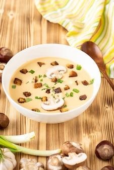 Tradycyjna francuska zupa krem z kasztanów z grzankami na drewnianym stole.