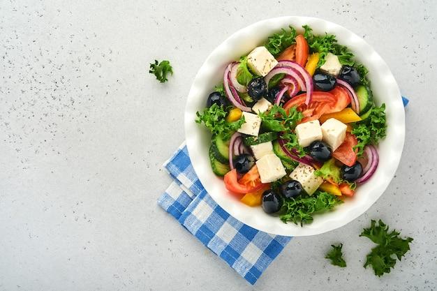 Tradycyjna grecka sałatka ze świeżego ogórka, pomidora, słodkiej papryki, sałaty, czerwonej cebuli, sera feta i oliwek z oliwą na białym talerzu. zdrowa żywność, widok z góry.