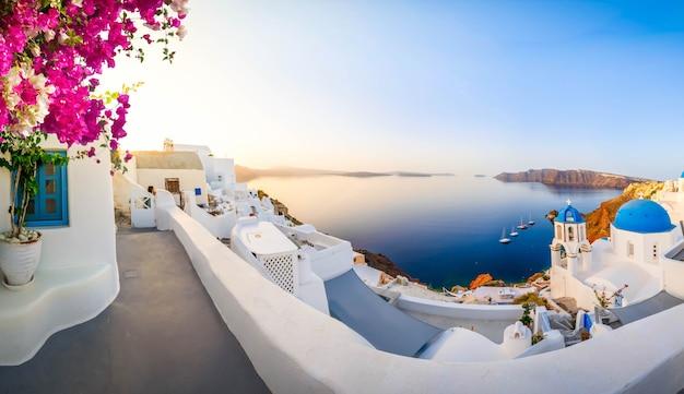 Tradycyjna grecka wioska oia na santorini, z niebieskimi kopułami na tle morza egejskiego i kalderą z kwiatami