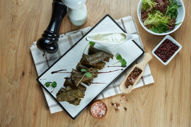 Tradycyjna gruzińska dolma - ryż z mięsem mielonym w liściach winogron na białym talerzu z sosem jogurtowym.
