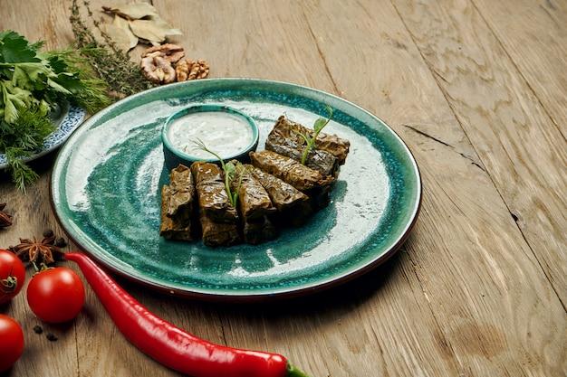 Tradycyjna gruzińska dolma - ryż z mięsem mielonym w liściach winogron na niebieskim talerzu z sosem jogurtowym. powierzchnia drewna. widok z góry. sarma