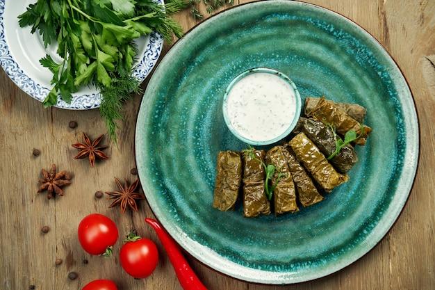 Tradycyjna gruzińska dolma - ryż z mięsem mielonym w liściach winogron na niebieskim talerzu z sosem jogurtowym. . widok z góry. sarma