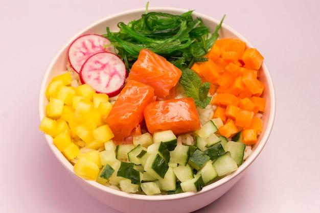 Tradycyjna hawajska czerwona miska rybna z ryżem, rzodkiewką, ogórkiem, pomidorem i wodorostami. miska buddy. dietetyczne jedzenie. leżał płasko. różowe tło.