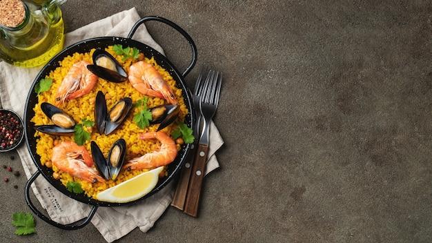 Tradycyjna hiszpańska paella z owocami morza na patelni z ciecierzycą, krewetkami, małżami, kalmarami. widok z góry.