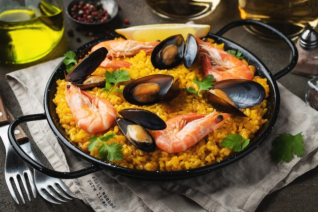 Tradycyjna hiszpańska paella z owocami morza na patelni z ciecierzycą, krewetkami, małżami, kalmarami.