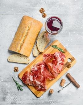 Tradycyjna hiszpańska szynka z ciabattą i czerwonym winem. na rustykalnej powierzchni.