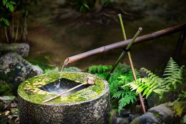 Tradycyjna japońska bambusowa fontanna przy ryoan-ji świątynią w kyoto, japonia