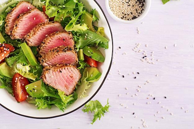 Tradycyjna japońska sałatka z kawałkami średnio rzadkiego grillowanego tuńczyka ahi i sezamu ze świeżym warzywem na misce.