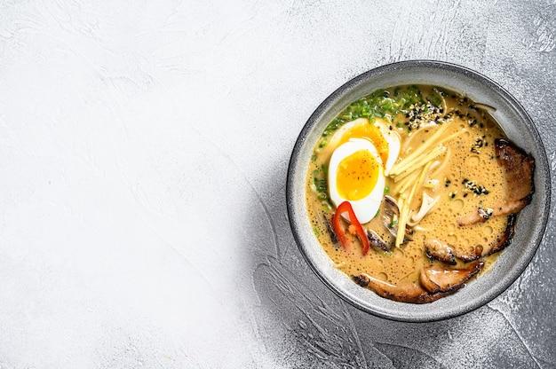 Tradycyjna japońska zupa ramen z rosołem mięsnym, makaronem azjatyckim, wodorostami, plastrami wieprzowiny, jajkami. białe tło