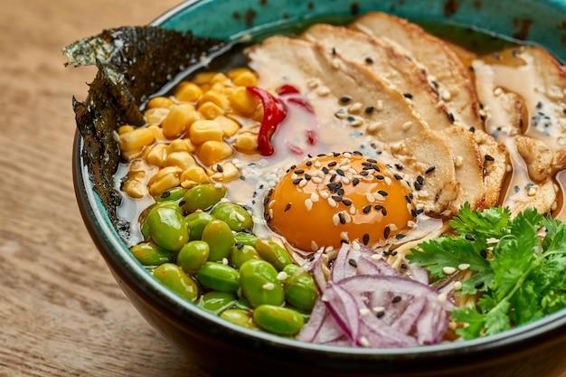 Tradycyjna japońska zupa ramen z żółtkiem i kurczakiem, warzywa w misce na drewnianym stole