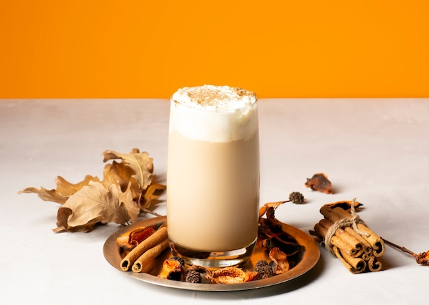 Tradycyjna jesienna przyprawa latte z dyni w szklance na metalowej tacy z przyprawami.