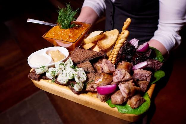 Tradycyjna kiełbasa, grzanki, smalec i sos na drewnianej tacy.