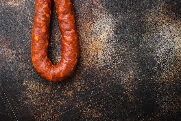 Tradycyjna kiełbasa salami chorizo na ciemnym tle, widok z góry z miejsca kopiowania.