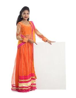 Tradycyjna kobieta trzyma i pokazuje pusty biały szyld lub tablicę na białym tle.