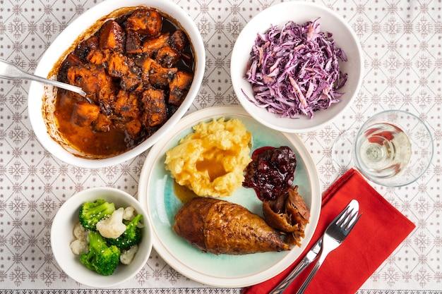 Tradycyjna kolacja dziękczynna z pieczonym indykiem, puree ziemniaczanym, sosem żurawinowym i warzywami
