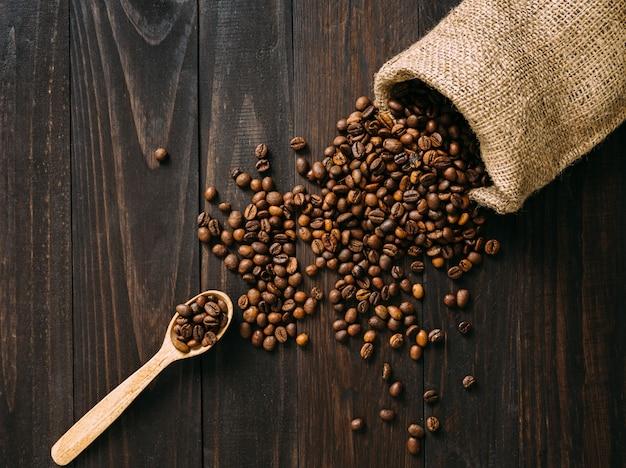 Tradycyjna koncepcja rozlewania ziaren kawy z naturalnego worka na ciemnym drewnianym stole