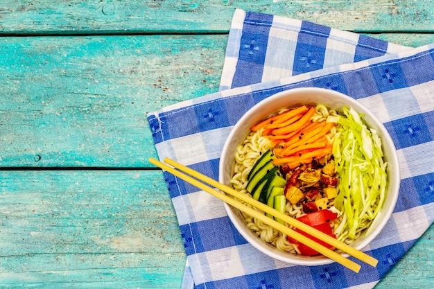 Tradycyjna koreańska miska na makaron z wędzonym kurczakiem, świeżymi pokrojonymi warzywami i sezamem