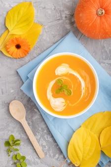 Tradycyjna kremowa zupa dyniowa zw białej misce na szarym tle betonu z niebieską serwetką