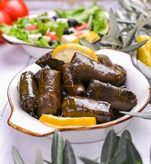 Tradycyjna kuchnia grecka. ryż owinięty w liście winogron. dolma z cytryną, przyprawami i sałatką grecką. domowe jedzenie. gałązki oliwne i różne pikantne przekąski