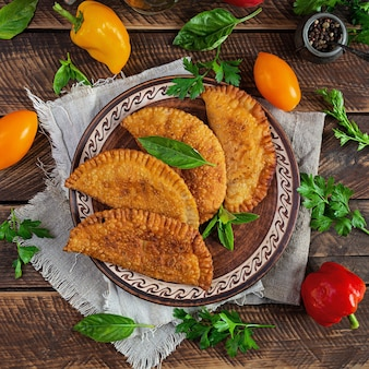 Tradycyjna kuchnia krymskotatarska, czebureki z mięsem z kurczaka. smażone empanady na drewnianym tle