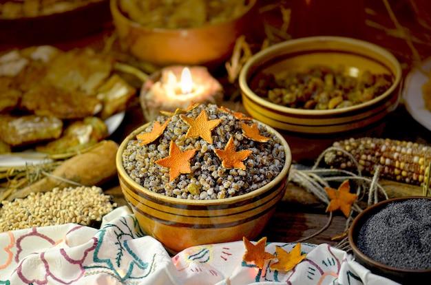 Tradycyjna kutya bożonarodzeniowa. słodki posiłek bożonarodzeniowy na ukrainie. gwiazda to jeden z symboli bożego narodzenia. świąteczna owsianka na podłoże drewniane.