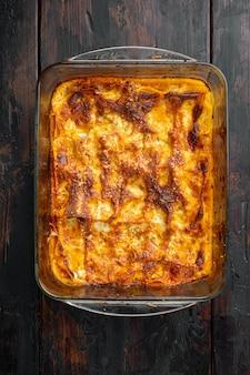 Tradycyjna lasagne z sosem bolońskim z mielonej wołowiny polana listkami bazylii na blasze do pieczenia