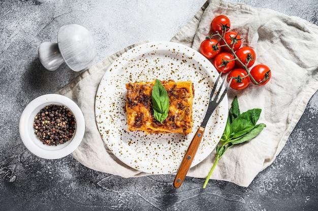 Tradycyjna lasagne zrobiona z mielonej wołowiny, sosu bolońskiego i beszamelu. szare tło. widok z góry