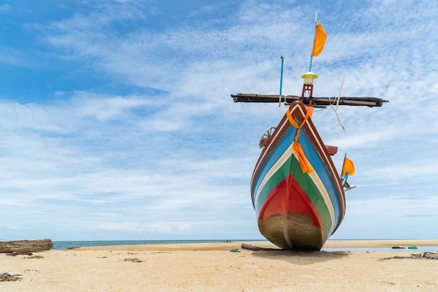 Tradycyjna łódź rybacka na plaży i niebieskim niebie