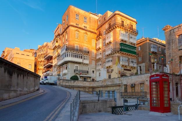 Tradycyjna maltańska ulica z czerwoną budką telefoniczną i budynkiem z kolorowymi okiennicami i balkonami o wschodzie słońca, valletta, stolica malty