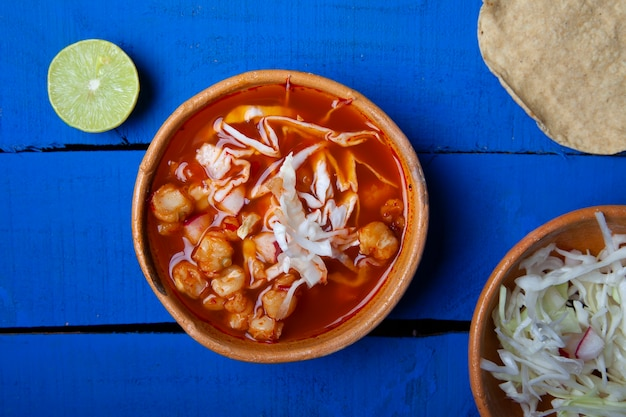 Tradycyjna meksykańska czerwona zupa pozole z tostadą i limonkami na niebieskim tle