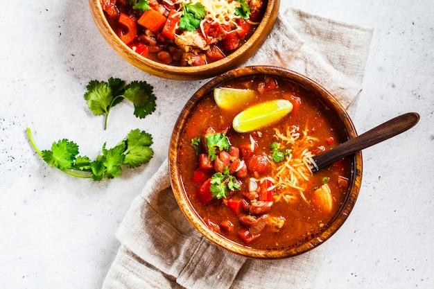 Tradycyjna meksykańska zupa fasolowa z mięsem i serem w drewnianej misce