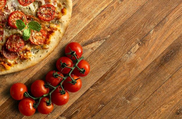Tradycyjna pizza pepperoni z kiścią pomidorów na drewnianej podstawie widok z góry