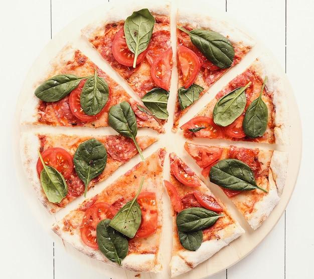 Tradycyjna pizza z plastrami pomidora i liśćmi bazylii