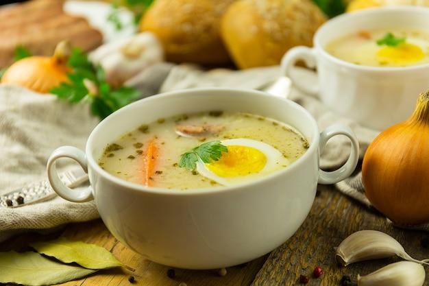 Tradycyjna polska zupa wielkanocna na drewnianym stole, z jajkiem i kiełbasą