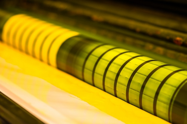 Tradycyjna prasa offsetowa. druk atramentowy w kolorach cmyk, cyjan, magenta, żółty i czarny. grafika artystyczna, druk offsetowy. fragment wałka wyciskowego w maszynie offsetowej czterech korpusów żółty