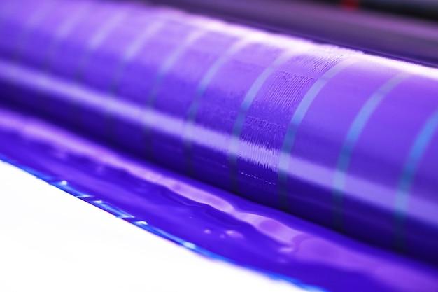 Tradycyjna prasa offsetowa. druk atramentowy w kolorach cmyk, cyjan, magenta, żółty i czarny. grafika artystyczna, druk offsetowy. prasa drukarska na maszynie offsetowej z czterema korpusami tuszu cyjan