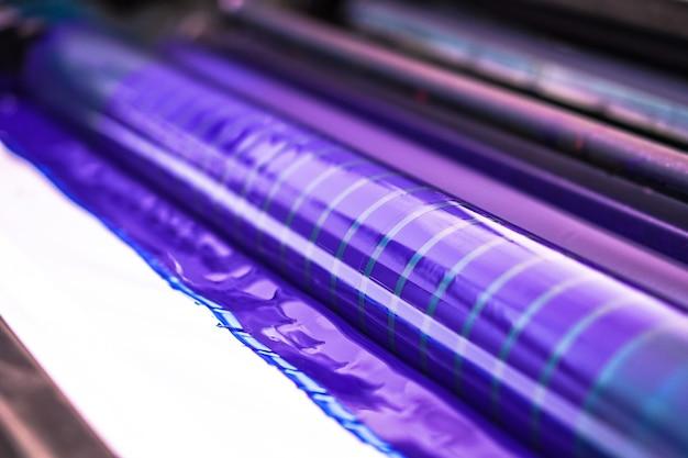 Tradycyjna prasa offsetowa. druk atramentowy w kolorach cmyk, cyjan, magenta, żółty i czarny. grafika artystyczna, druk offsetowy. szczegół wałka drukarskiego w maszynie offsetowej z czterema korpusami z niebieskim tuszem