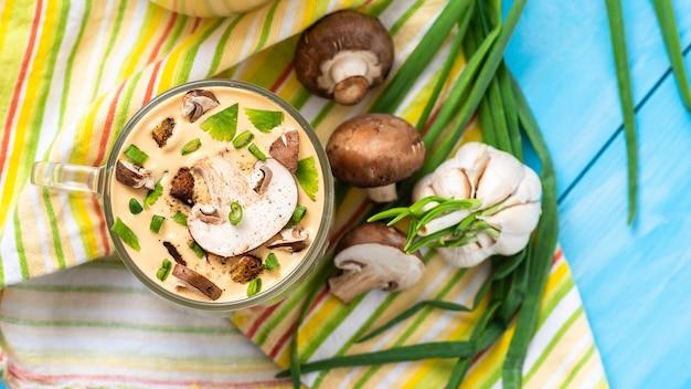 Tradycyjna pyszna zupa grzybowa z siekanymi grzybami na niebieskiej drewnianej powierzchni