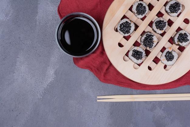 Tradycyjna rolka sushi maki z pałeczkami i sosem sojowym na czerwonym obrusie.