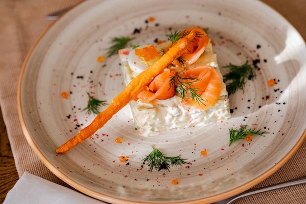 Tradycyjna rosyjska sałatka olivier. sałatka ozdobiona jest łososiem i jajkiem przepiórczym.