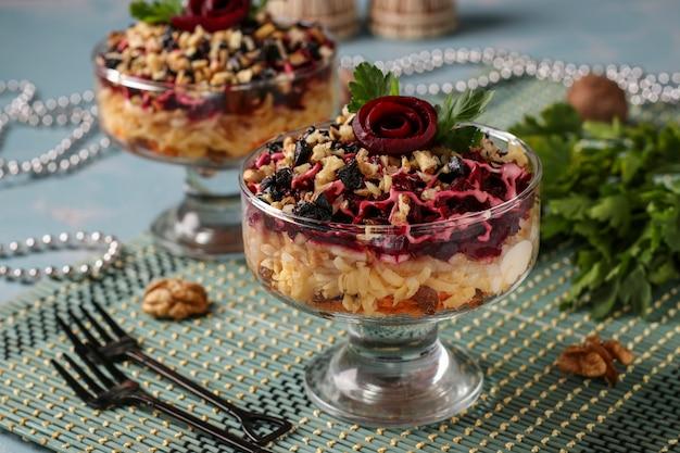 Tradycyjna rosyjska sałatka z serem, burakami i marchewką, ozdobiona różami buraczanymi, orzechami i suszonymi śliwkami, porcja, orientacja pozioma