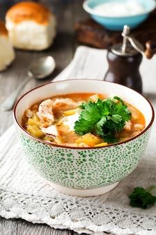 Tradycyjna rosyjska zupa rassolnik ogórek kiszony, jęczmień, kurczak, pomidory i pietruszka w ceramicznej misce