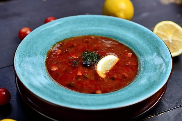 Tradycyjna rosyjska zupa solanka z mięsem, kiełbaskami, warzywami, kaparami, ogórkami kiszonymi i oliwkami z cytryną, przyprawami i przyprawami