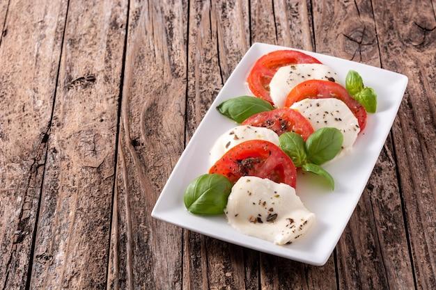 Tradycyjna sałatka caprese na białym talerzu