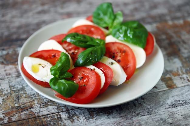 Tradycyjna sałatka caprese z mozzarellą pomidorową i bazylią.