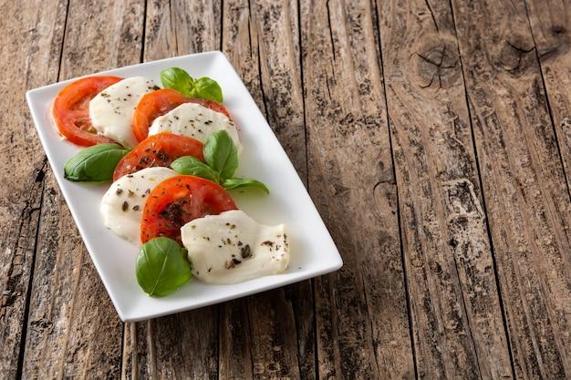 Tradycyjna sałatka caprese z pomidorami i mozzarellą na rustykalnym drewnianym stole