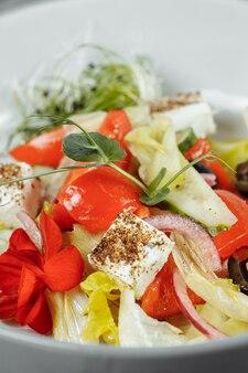 Tradycyjna sałatka grecka ze świeżymi warzywami, serem feta i oliwkami. widok z góry. selektywna ostrość.